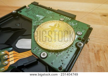 Cryptocurrency Golden Bitcoin On Hard Disk Drive With Blur Background
