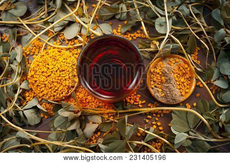 Close Up Of Fenugreek With Its Seeds And Powder And The Extracted Water On A Wooden Surface In Dark