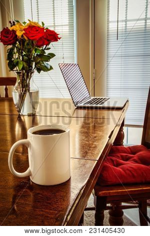 A Coffee Cup, A Computer, Floweres, All Sitting On A Table.