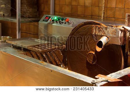 Liquid Hot Chocolate On The Conveyor Line. Working Machine On Confectionery Factory. Automated Food