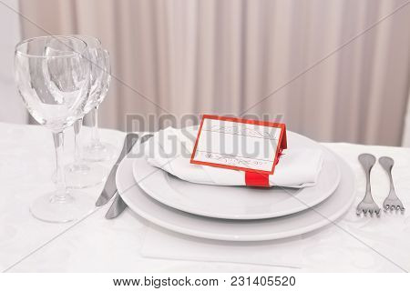 Elegant Decoration Of Table In A Restaurant. Place Card On The White Festive Table. Napkins, Fork An