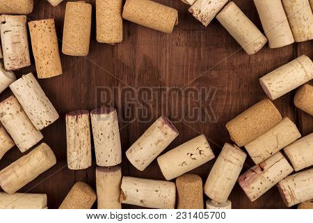 Many Wine Corks, Forming A Frame On A Dark Wooden Background Texture, With A Place For Text. A Desig