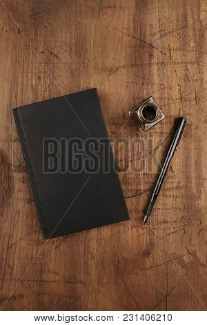 An Overhead Photo Mockup Of A Black Book On A Dark Rustic Background, With A Fountain Pen, An Ink We