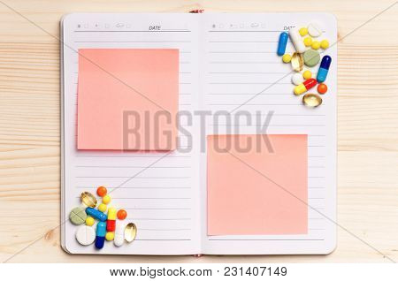 Blank notepad with pills on the wooden table. View from above