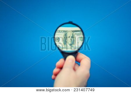 Hand With A Magnifying Glass Increases A Small Us Dollar Banknote, Blue Background. Optical Distorti