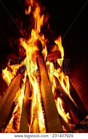 Burning Firewood On A Dark Background In The Fireplace.