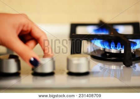 Woman Hand Turning On The Stove Flame