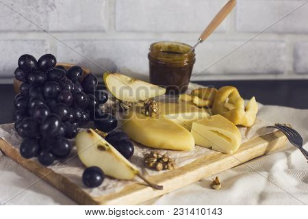 Cheese, Honey, Grapes, Pears And Nuts On Wooden Board On Kitchen
