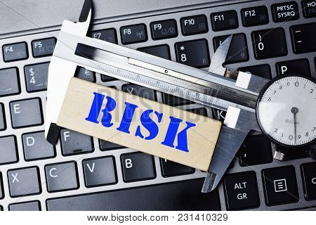 Risk Assessment Or Measuring The Risk Concept With High Precision Caliper Tool On Laptop Keyboard