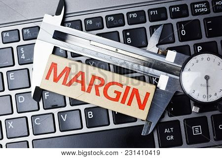 Measure Margin Of Profit Concept With Caliper Tool On Computer Keyboard