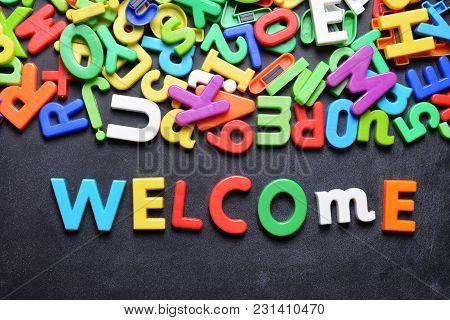 Welcome Message Written With Colorful Plastic Letters On Chalkboard Or Dark Background