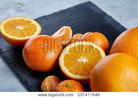 Pile Of Whole And Half Cut Fresh Tangerine And Orange On Black Stone Cutting Board Over White Textur