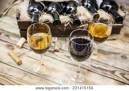 Three Glasses Of Wine On A Wooden Table. Wine Of A New Harvest Background