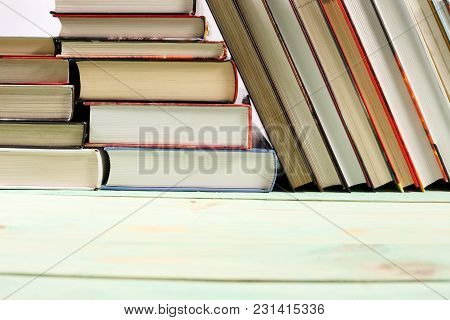 Pile Of Various Books On Wooden Background. With Copy Space For Your Text