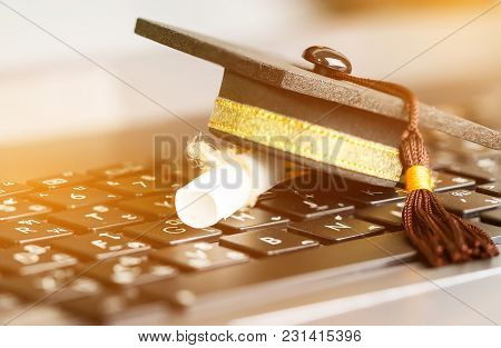 E-learning Online Graduate Education Concept : Graduation Cap, Certificate Degree On Laptop Computer