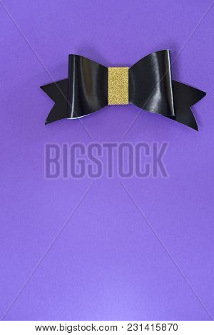 Black And Golden Bow Tie Over Ultra Violet Background. Copy Space. Free Space For Text