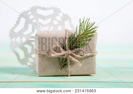 Gift Box Wrapped Kraft Paper Tied With Twine And Paper Snowflake And Tied With Twine. With Copy Spac