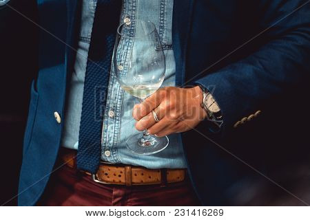 Wine Tasting In A Restaurant. Man In A Blue Suit Holds Glass Of White Wine