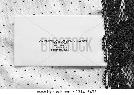 Care Clothes Label On Black And White Textile Background Closeup