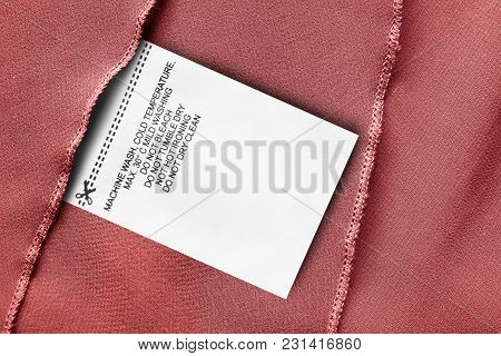 Care Clothes Label On Red Silk Background Closeup