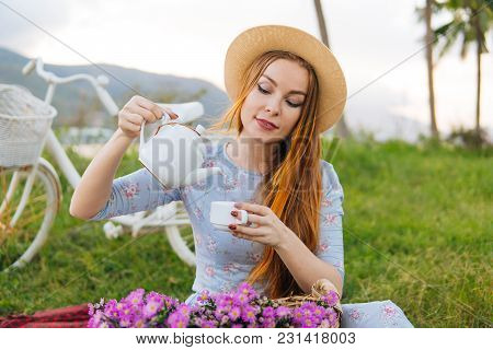 Woman With Teapot And Flowers, Enjoying Picnic. Female Drink Tea Outdoors. Bicycle On Background