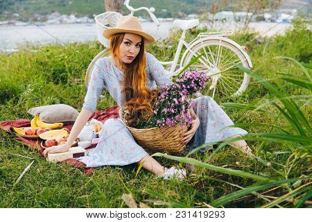 Woman With Red Hair In Blue Dress And Hat With Flowers, Enjoying Picnic. Sea And Bicycle On Grass On