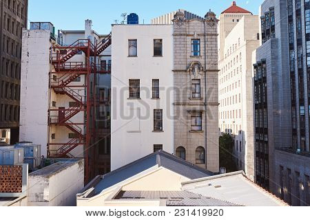 Rooftops And The Back Of Buildings On A Street In The Downtown District Of A City On A Sunny Day