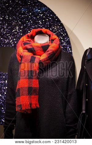 Mannequin With A Patterned Red Scarf And A Warm Woolen Sweater In A Shop Showcase