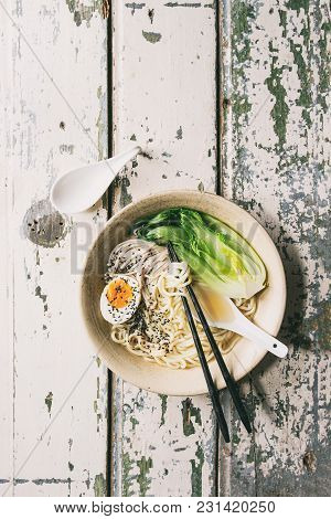 Asian Dish Udon Noodles With Boiled Egg, Sesame, Mushrooms, Boc Choy Served In Ceramic Bowl With Spo