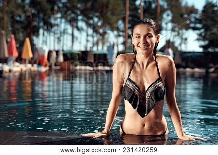 Young Cute Girl Is Spending Time In Pool. Summer Vacation Of Happy Girl At Swimming Pool. Swimming P