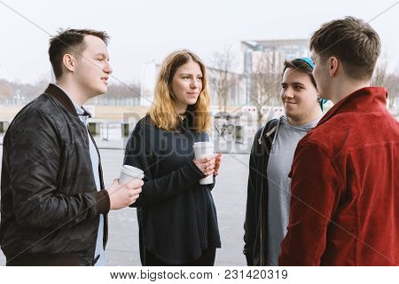 Group Of Teenage Friends Having A Conversation While Standing Together On City Street Holding Coffee