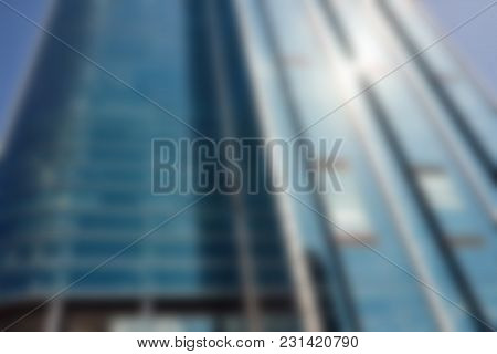 Low Angle Exterior Of Defocused Tall Modern Glass Skyscraper Against A Blue Sky In The Commercial Di
