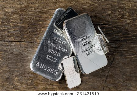 Silver Bullion On Wood Texture Background. Coins And Bars.