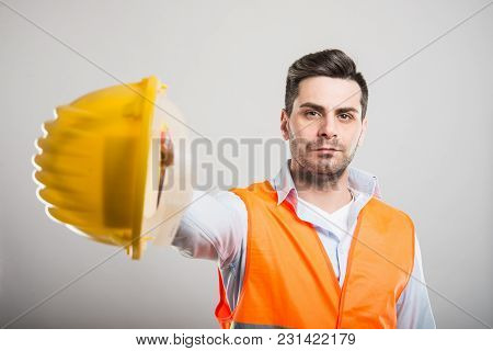 Portrait Of Architect Handing Yellow Hardhat
