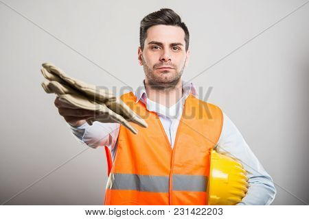Portrait Of Architect Handing Pair Of Working Gloves