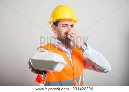 Portrait Of Architect Handing Bad Smelling Lunch Box
