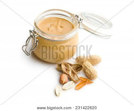 Peanut butter in jar and peanuts isolated on white background.