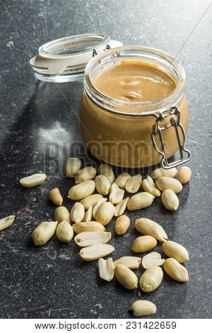 Peanut butter in jar and peanuts on old kitchen table.