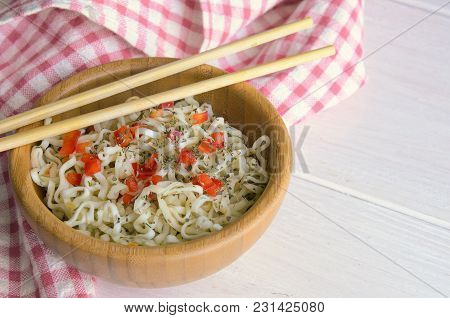 Instant noodles with on wooden bowl and chopsticks on white background with copy space. Typical Asia