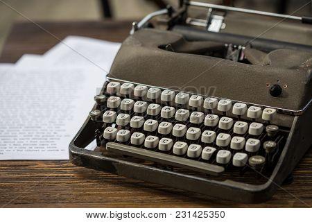 Gray Retro Typewriter With White Keys On Wooden Tabletop.