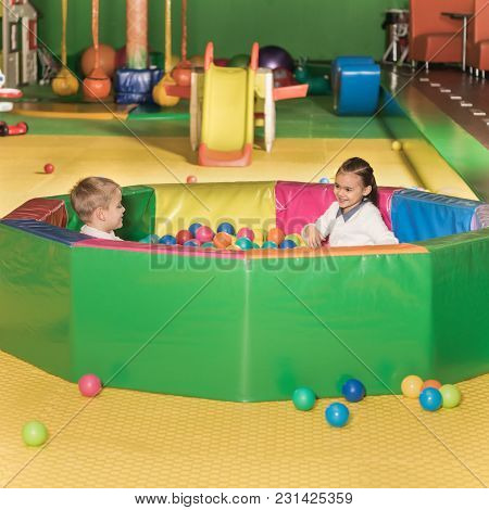 Adorable Happy Little Children Playing In Pool With Colorful Balls