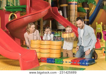 Happy Family With Two Children Playing Together In Entertainment Center