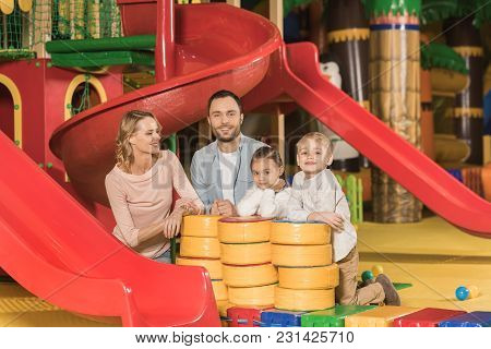 Happy Family With Two Kids Smiling At Camera While Playing Together In Entertainment Center