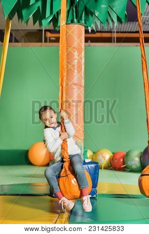 Cute Little Kid Swinging On Swing In Entertainment Center