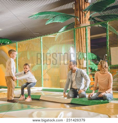 Parents Looking At Cute Little Children Playing Together In Entertainment Center