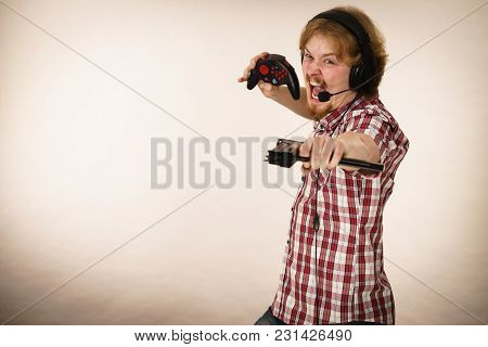 Nerd Geek Young Adult Man Playing On The Video Console Holding Gun Wearing Headphones With Microphon