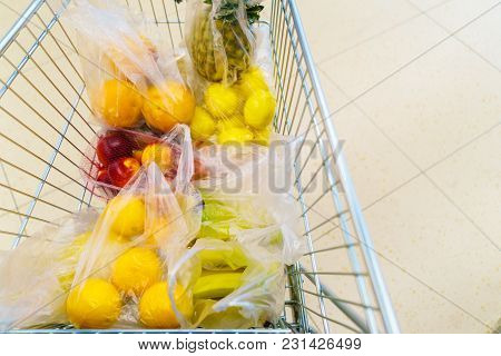View From Shopping Cart Trolley Basket At Supermarket Self Service Grocery Shop. Fruits And Vegetabl