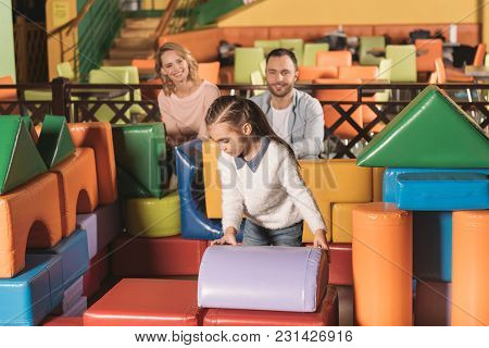 Parents Looking At Cute Little Daughter Building Castle With Colorful Blocks In Entertainment Center
