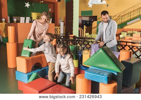 Happy Family With Two Children Playing With Colorful Blocks In Game Center