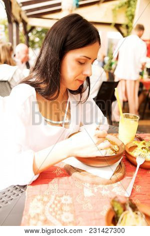 Young woman is eating in indie restaurant.